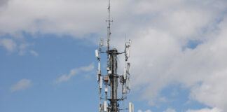 Cell tower standing alone against clouds