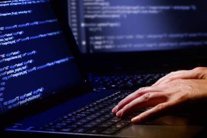 Hands on keyboard showing computing code