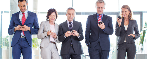 Business partners texting on their phones.