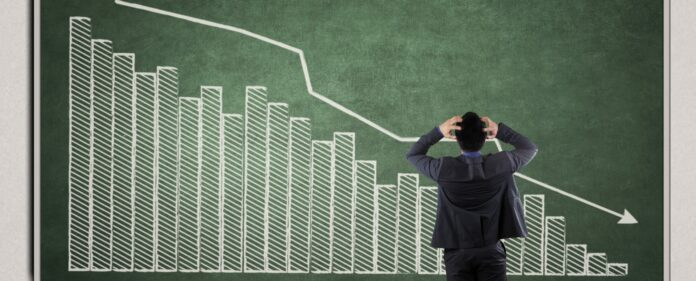 A businessman looks at a chart showing declining sales.