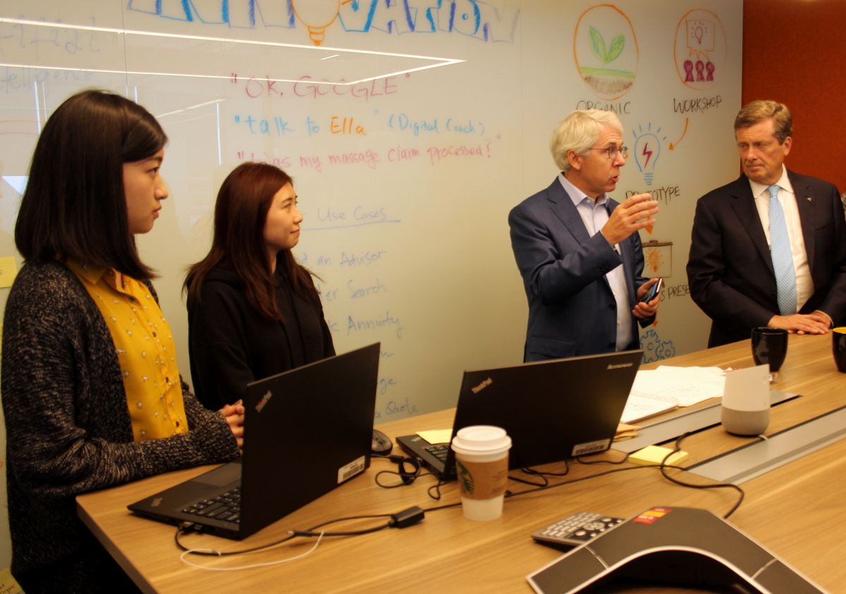 Sun Life CEO Dean Connor (centre), alongside his development team, shows off digital coach Ella to Toronto Mayor John Tory.