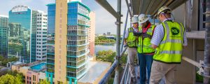 3 Construction Workers Using iPad on High-rise Rooftop 16-3