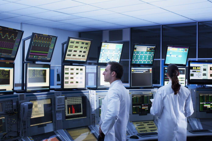 Scientists monitoring computers in control room