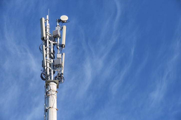 A cell tower stands against a blue sky
