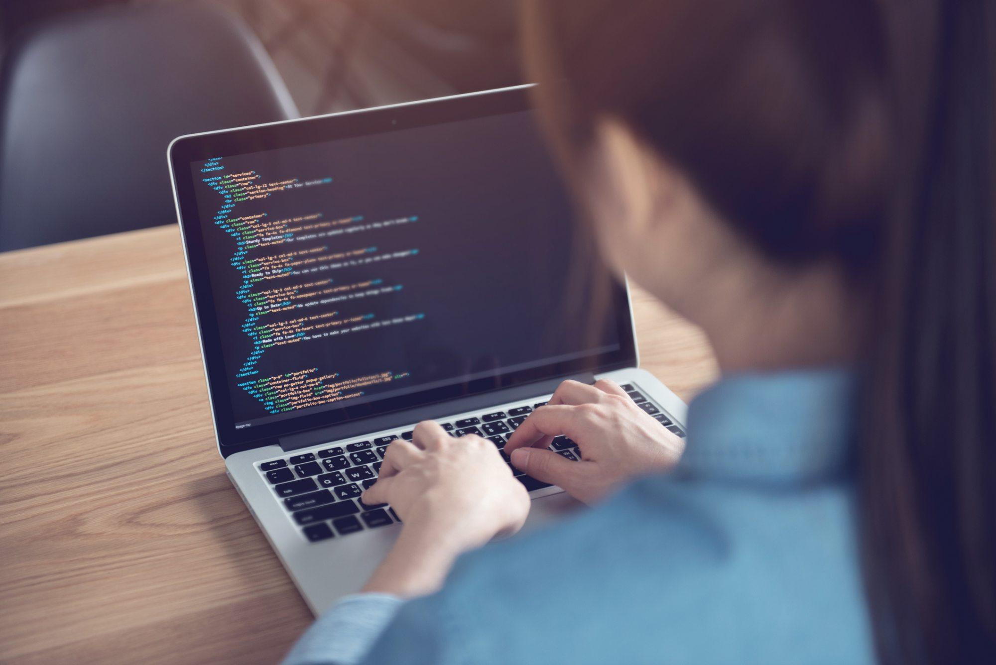Women typing code on laptop
