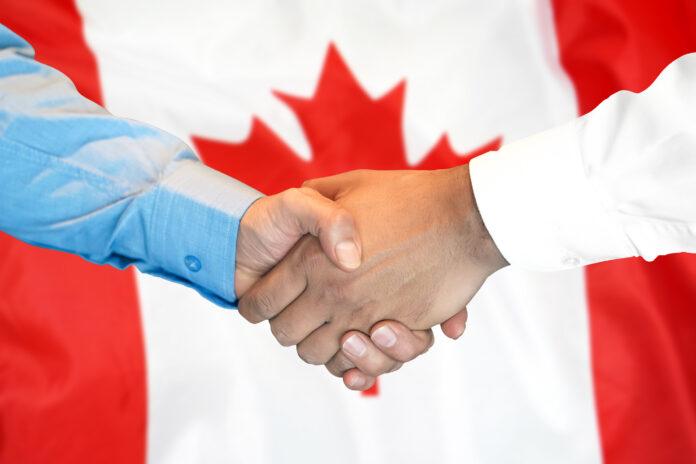 Photo of handshake on Canada flag background