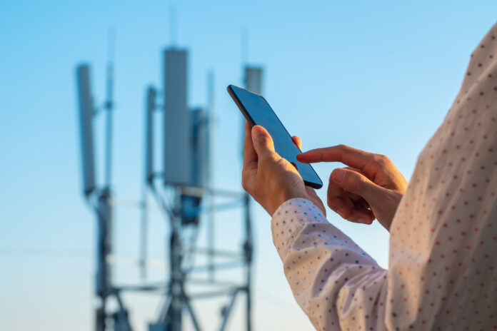 a smartphone against a 5G celltower as backdrop