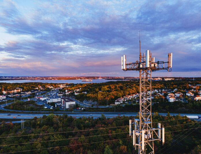 Drone shot of a cell tower at sunset overlooking a suburban area