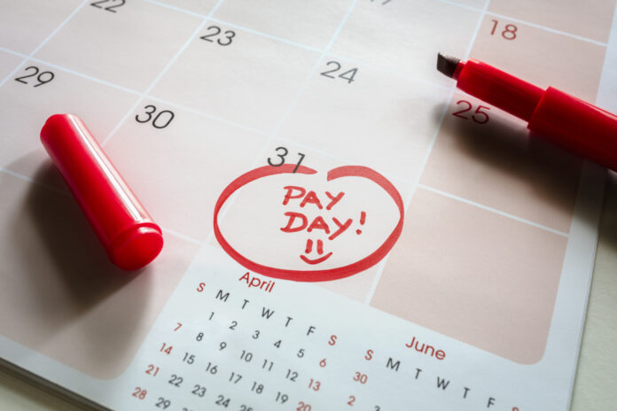 Photo of Payday end of month date on calendar with red marker and circled day of salary